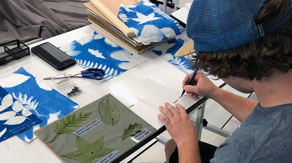 a student in an art studio making prints