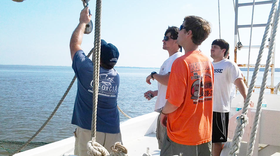 students hauling in a shrimp line on a boat in the ocean